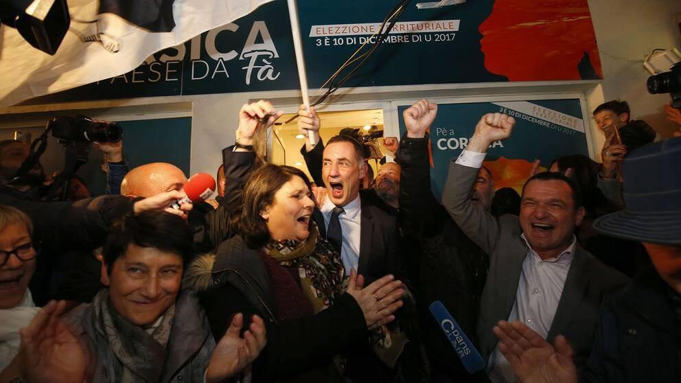 Pè a Corsicas toppnamn Gilles Simeoni (i mitten) firar valframgångarna med sina anhängare.
