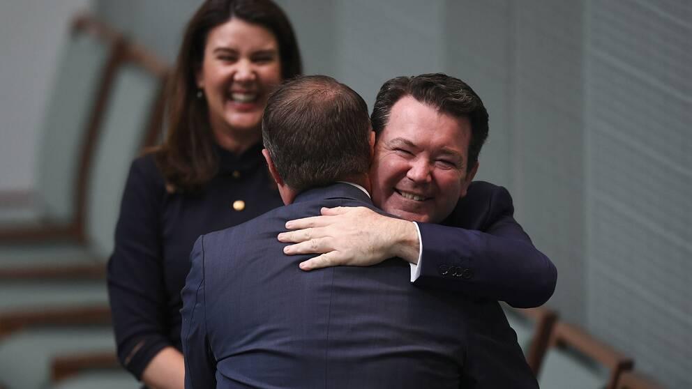 Ledamoten Tim Wilson kramas om av kollegan Dean Smith, efter Wilsons frieri till sin partner Ryan Bolger (ej i bild).
