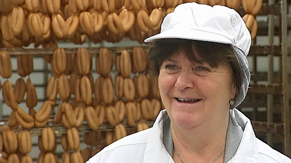 Birgitta Starck i vit rock och vit keps framför ställ med prinskorv