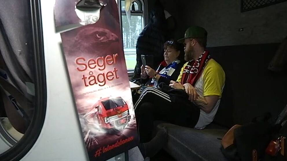 Två personer som sitter i en tågkupé.