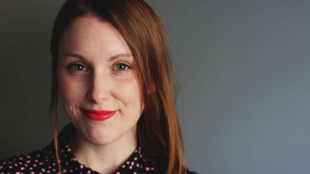 Julia Tuvesson ler och tittar rakt in i kameran. Röda läppar och rödlätt långt hår.