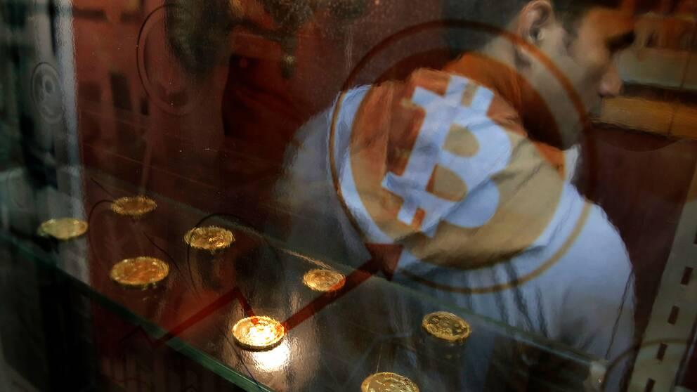 Man vid uttagsautomat för Bitcoin.
