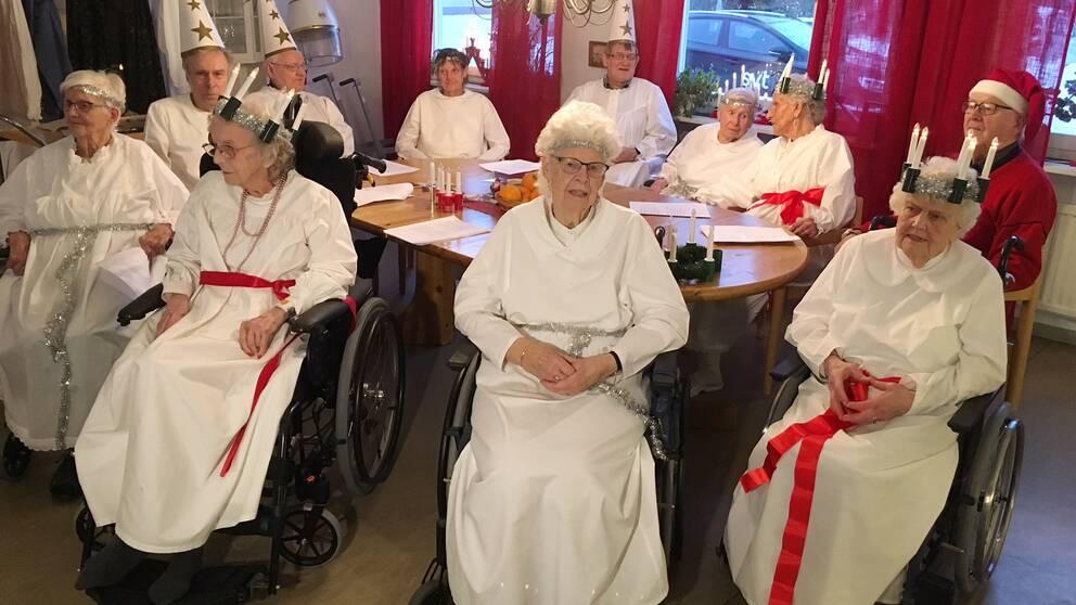 Äldre personer i rullstolar och luciakläder.
