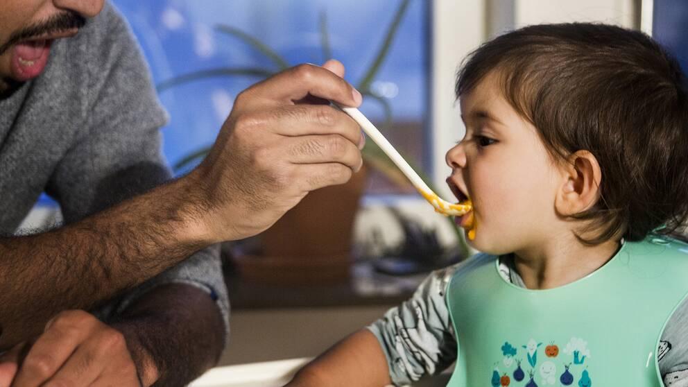 Barn matas av sin pappa.