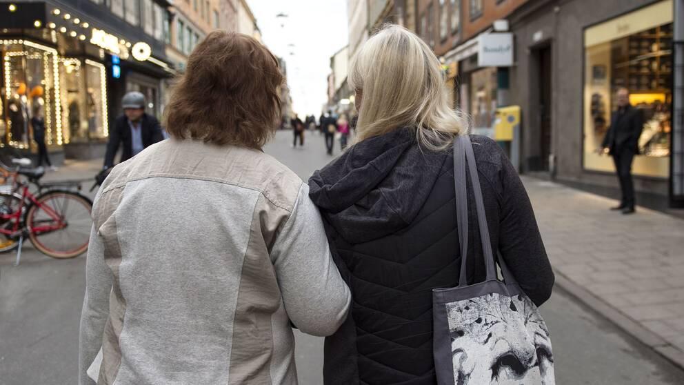 Två kvinnor går arm i arm i stadsmiljö