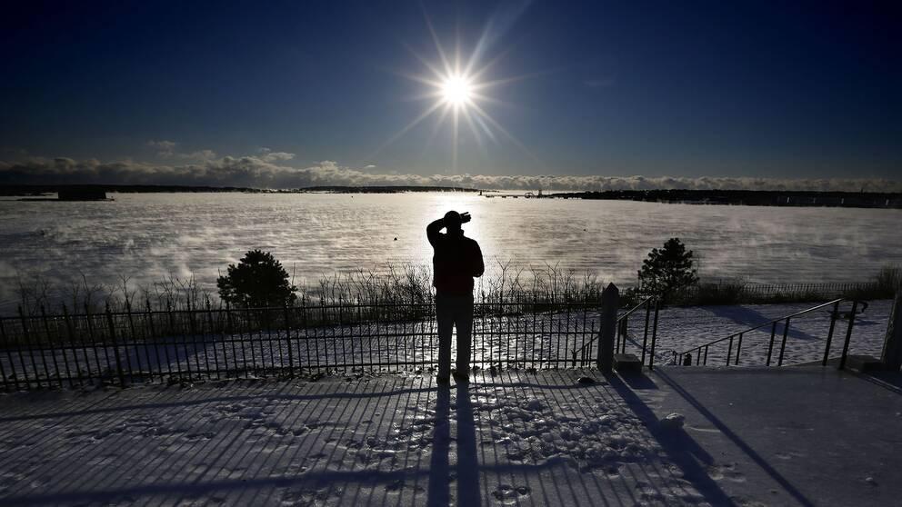En man står och tittar mot solen.