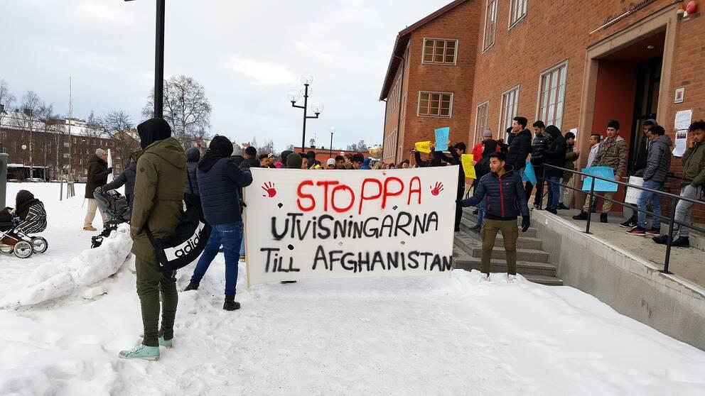 ungdomar protesterar. håller plakat med texten stoppa utvisningarna till afghanistan