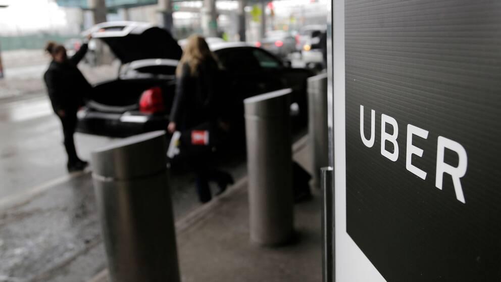 Två kvinnor vid en bil bakom Ubers logotyp