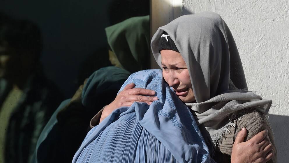 Två kvinnor sörjer sina anhöriga på ett sjukhus efter attacken i Kabul.