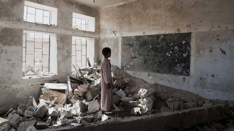 En ensam pojke står i en hög av ruiner av det som en gång var ett klassrum.