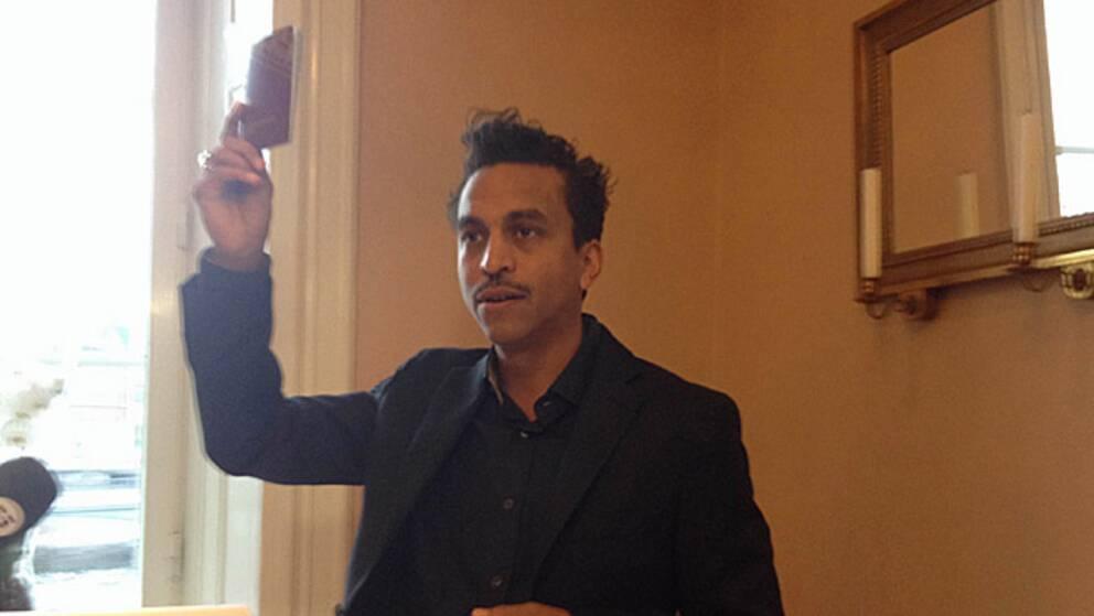 """En rörd Timbuktu håller upp sitt pass i riksdagen. """"Jag kommer att älska i Sverige, jag kommer att leva i Sverige och jag kommer dö i Sverige"""", säger han vid prisutdelningen."""