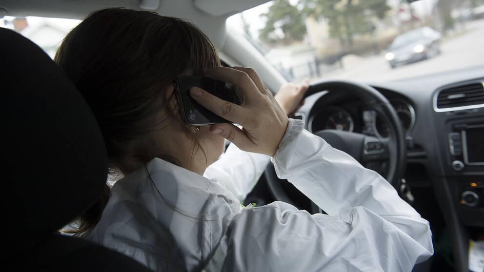 Bilist som talar i telefon