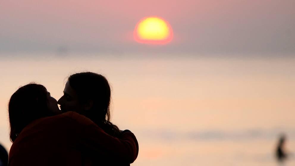 Siluetter av par som kysser varandra med solnedgång i bakgrunden.