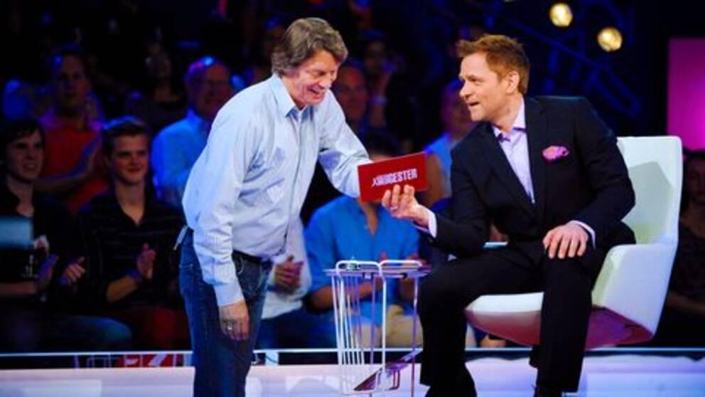 En bild som visar Johannes Brost som deltagare i Gäster med gester tillsammans med programledaren Rickard Olsson.