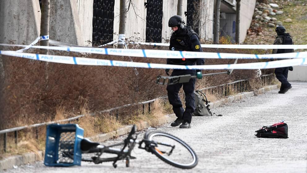 Polisen undersöker det avspärrade området. En man i 60-årsåldern avled och en kvinna i 45-årsåldern skadades i en explosion vid tunnelbanestationen Vårby Gård utanför Stockholm.