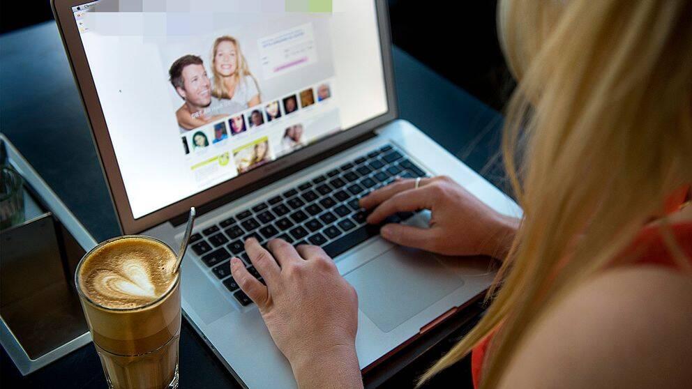 En kvinna sitter vid en dator och surfar på en sajt för nätdejting.