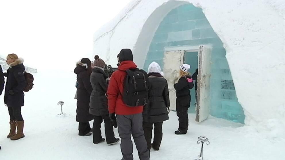 En grupp människor framför ett ishotell.