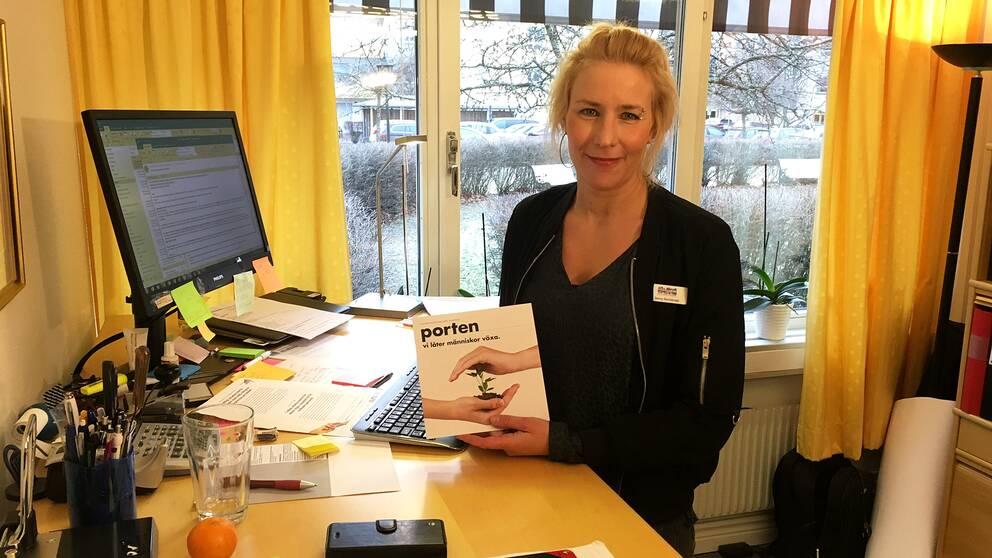 """Jenny Nordansjö står i mitten av bilden, i kontorsmiljö. Hon håller upp något med ordet """"Porten"""" på."""
