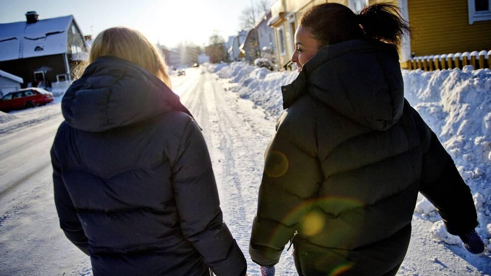 Två kvinnor går längs med solig snötäckt gata.