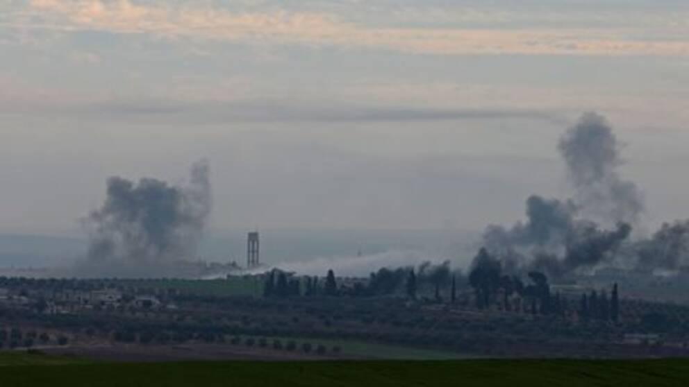 Rökmoln från flygbomber stiger från flera platser i en stad i syriska provinsen Idlib.