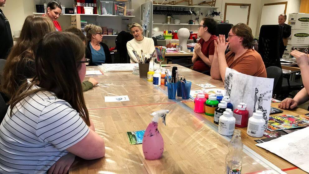 Ett bord i mitten av bilden, penslar och färger står på bordet. Runt bordet sitter människor, bland annat Lars Lerin