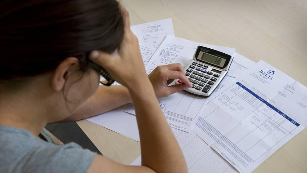En kvinna sitter med räkningar framför sig.