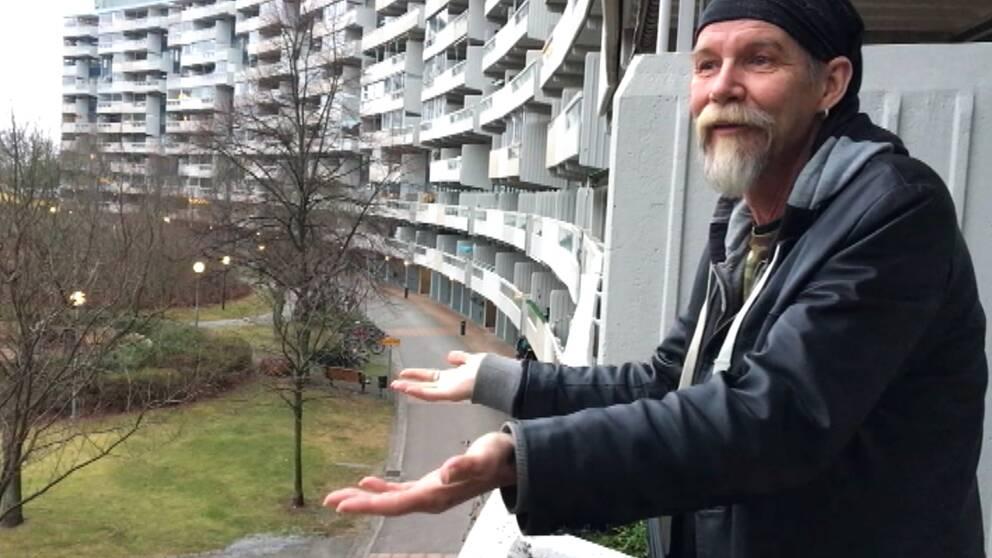 Kenneth Forsman står med utslagna händer mot ett litet grönområde intill ett stort antal lägenheter