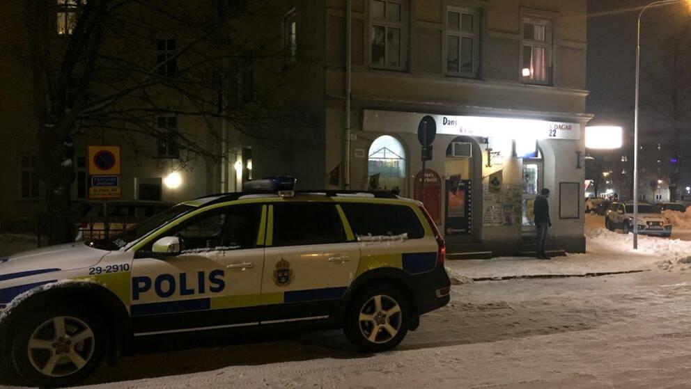 En polisbil syns närmast kameran. Till höger syns lampor på en vägg