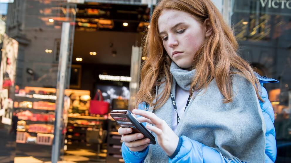En kvinna tittar på sin mobiltelefon.
