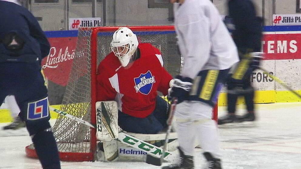En ishockeyrink. En målvakt syns i mitten med spelare runt omkring sig
