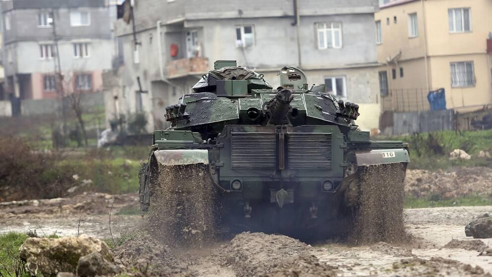 En grön turkisk stridsvagn som åker nedför en lerväg.