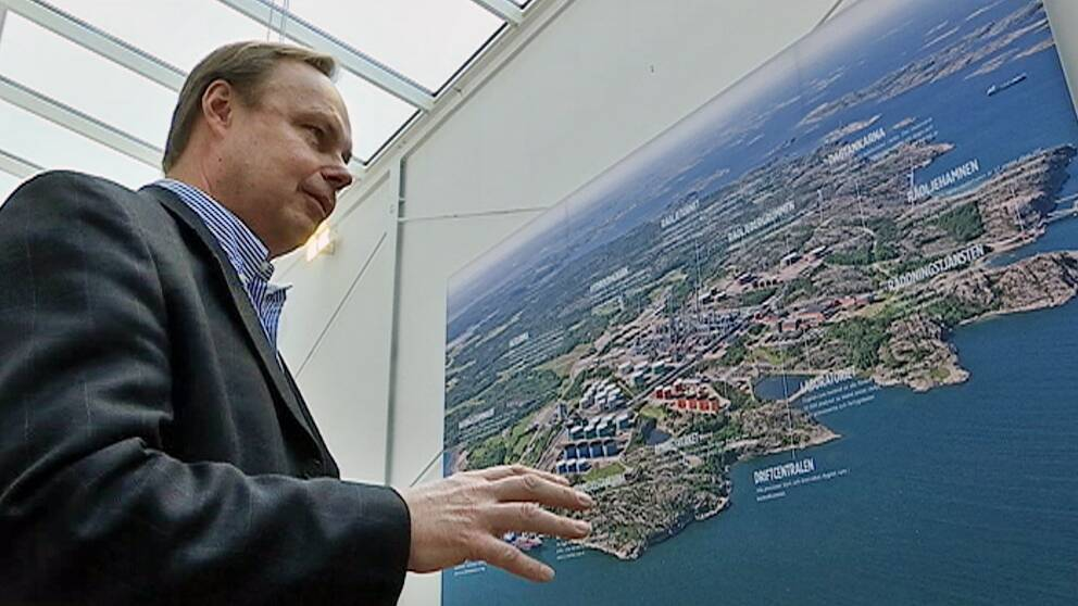 Peter Abrahamsson intill flygbild av preemraffs anläggning i Lysekil.
