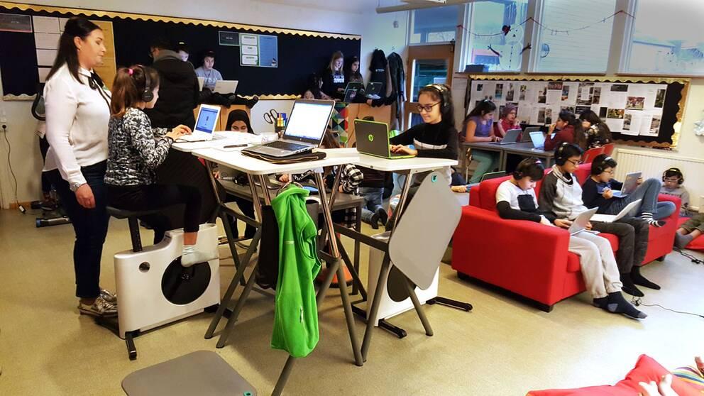 Klassrum med elever som sitter i soffor och på träningscyklar