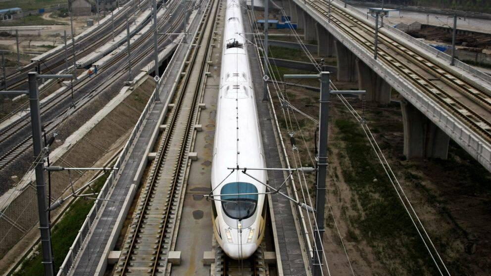 Ett vitt höghastighetståg står stilla på ett tågspår.