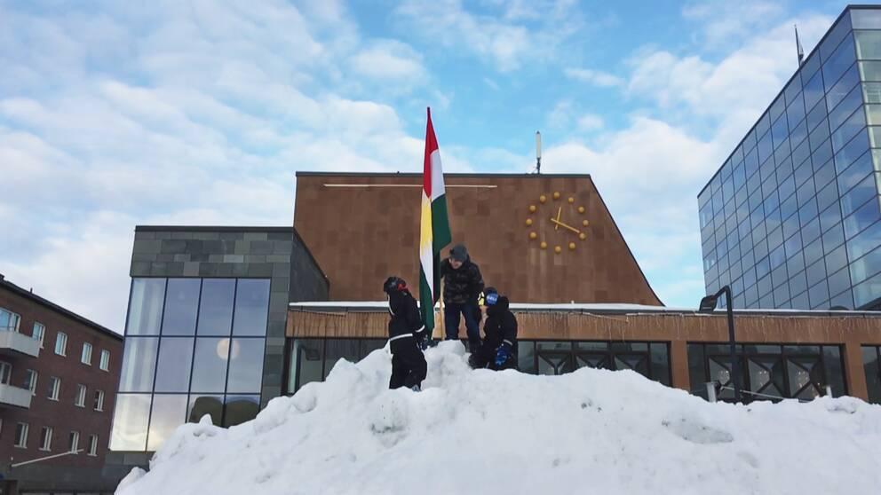 tre barn på snöhög reser flagga, byggnader bakom