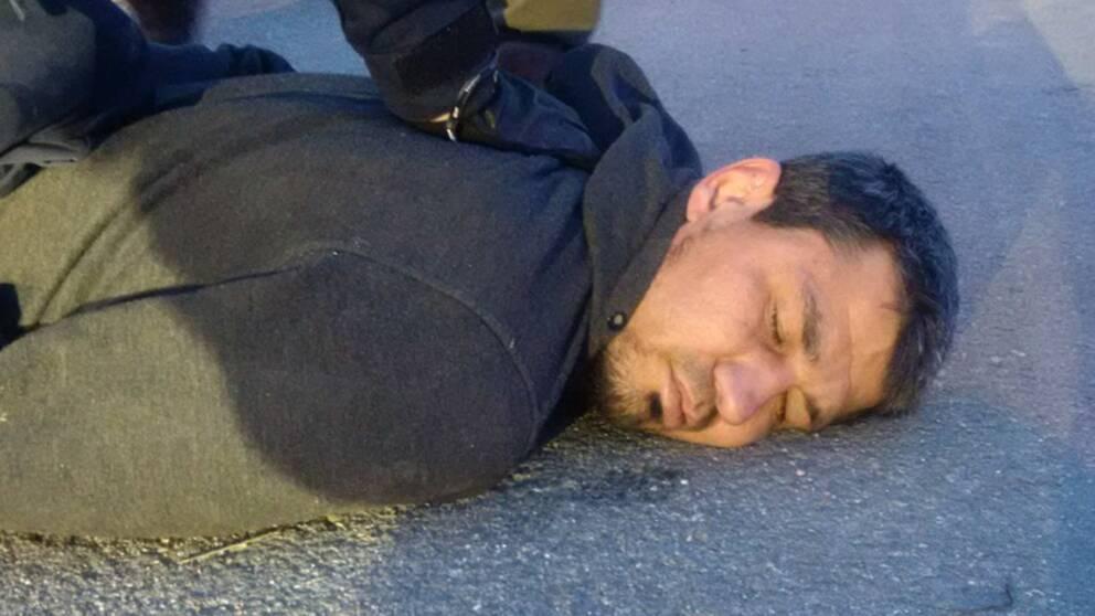 En bild föreställande misstänkte terroristen Rakhmat Akilov liggandes på asfalt med polisers armar över sig.