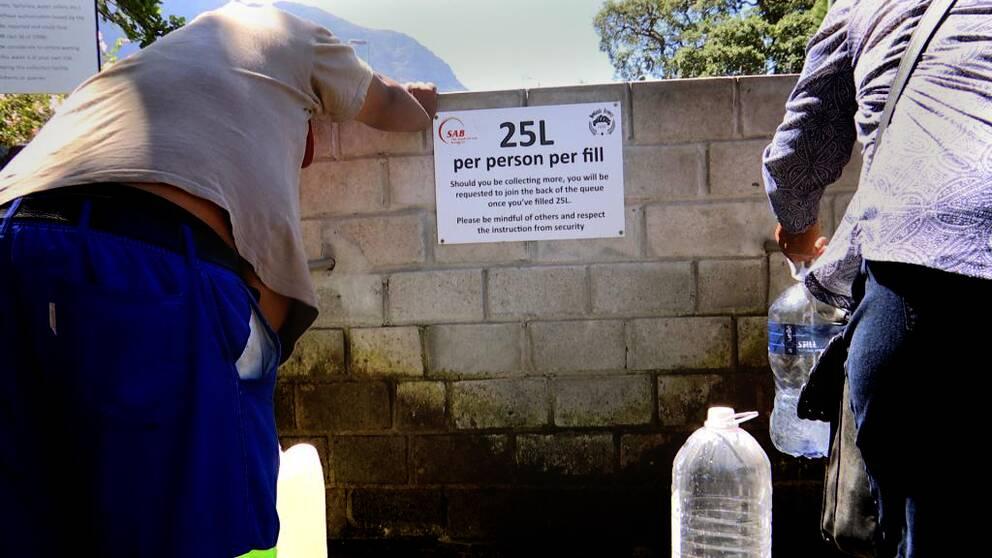 Två personer fyller sina dunkar vid vattenkällan i Newlands i Kapstaden.