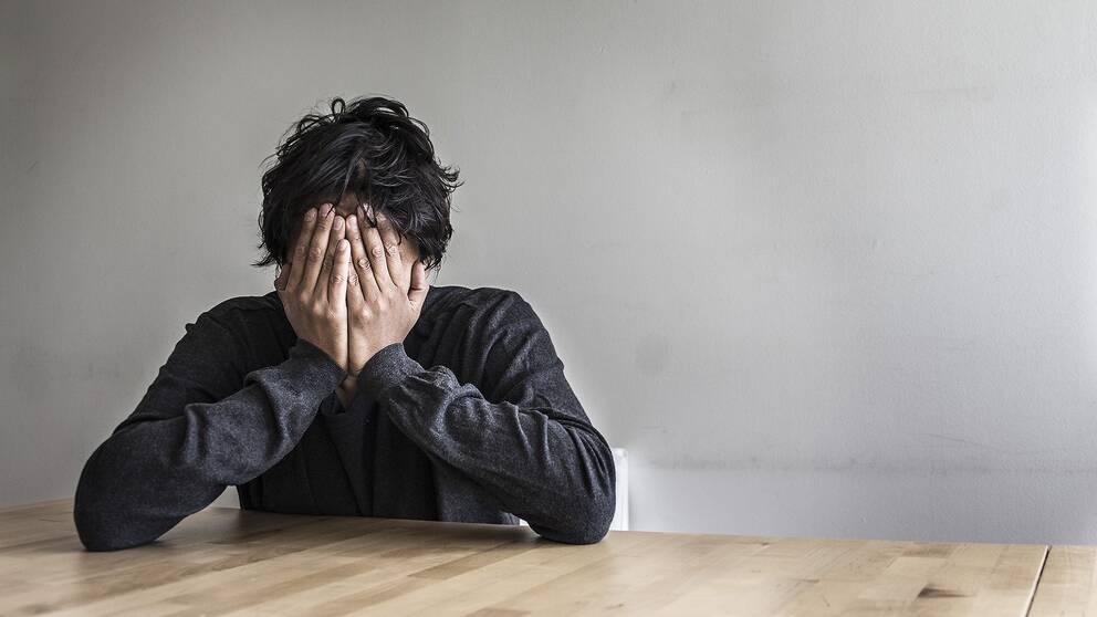 En kille sitter vid ett bord med ansiktet i händerna.