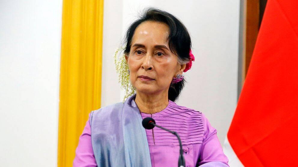 Aung San Suu Kyi står i ett talarpodium med blommor i håret.