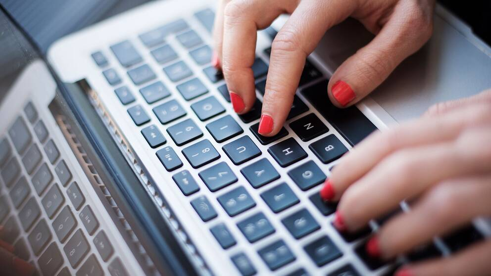 Kvinnohand skriver på laptop.