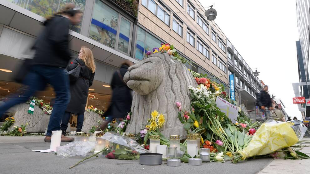 Blommor på ett betonglejon på Drottninggatan efter dådet.