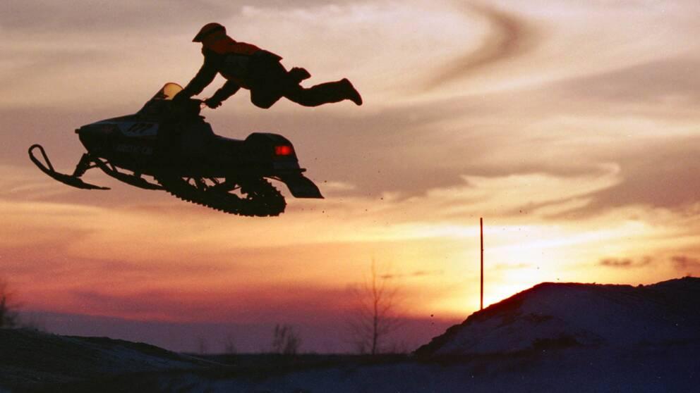 Skoterförare hoppar med sin snöskoter