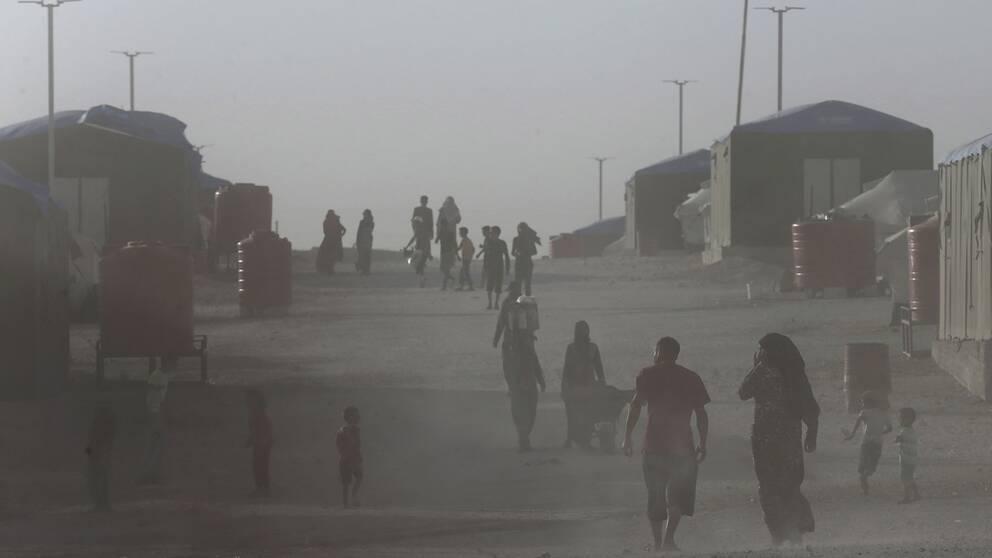 Ett dammigt läger i norra Syrien där människor går nedför en väg med tält på varje sida.