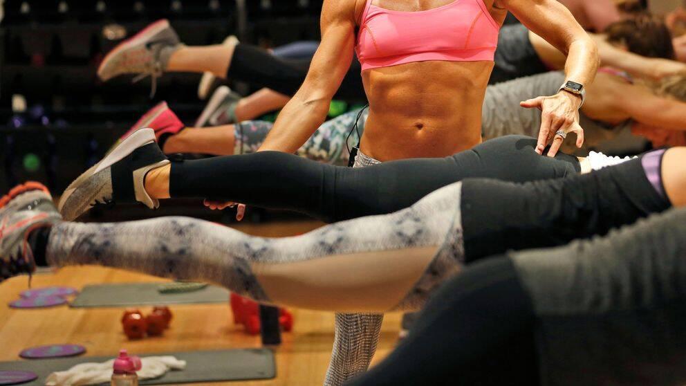 Muskulös kvinna står i mitten med andra kvinnor runt sig som hon instruerar på ett gym.