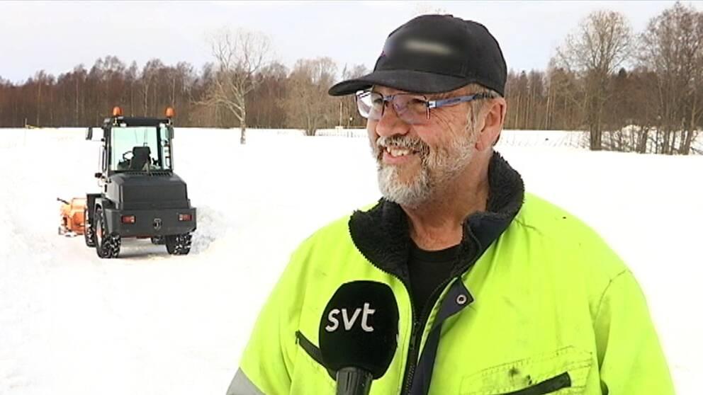 en leende man står på isen, liten traktor i bakgrund
