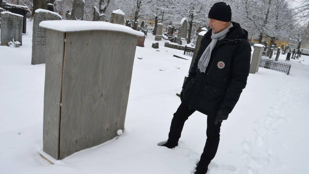 Kyrkogårdschefen Torleif Örn står på en snöig kyrkogård och tittar på en låda av trä som satts utanpå en gravsten. På toppen av lådan har några centimeter snö samlats.