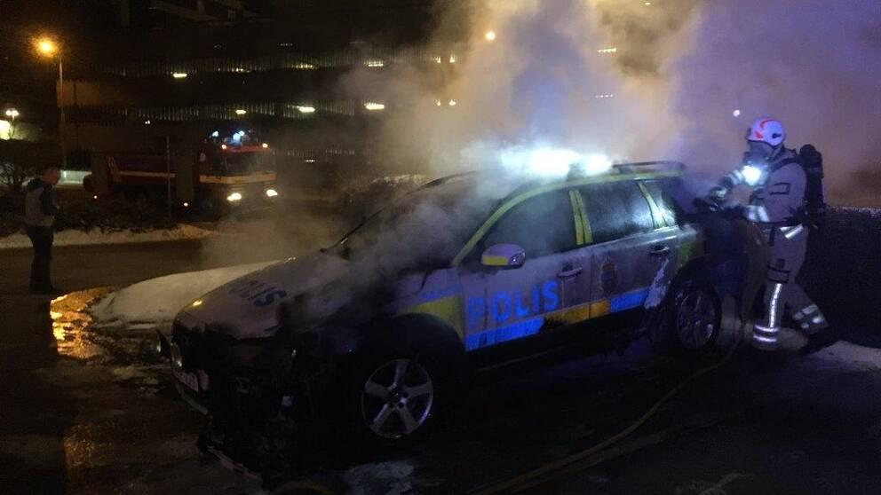 Polisbil brinner utanför polisstationen i Trollhättan den 23 februari 2018.