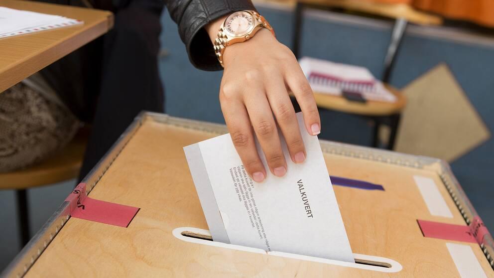En kvinna röstar i en vallokal.