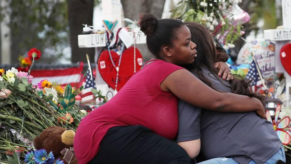 Två personer sitter på huk och kramas. I bakgrunden syns mängder av blommor och minnesmärken.