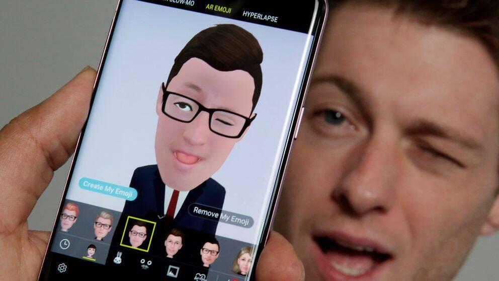 Mobiltelefon med app som gör om ditt ansikte till en emoji.